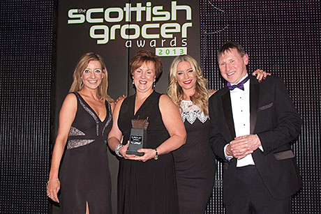 Lee Schofield, Imperial Tobacco's regional sales manager for Scotland, left, and Denise Van Outen, second right, present the Scottish Grocer Tobacco Retailer of the Year award to Broadway Convenience Store.