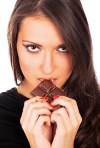 sh young woman eating chocolate serious