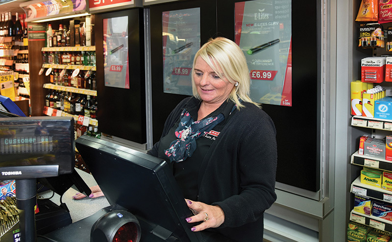 Spar Leven Street Motherwell Staff member woman at till with vending gantry in background