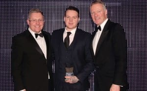 Jim Young, sales director, off-trade for Tennent Caledonian Breweries, left, and awards event host Rory Bremner, right, present the Scottish Grocer 2015 Store Manager of the Year Award to Gerry Haughey of Spar Thornliebank.