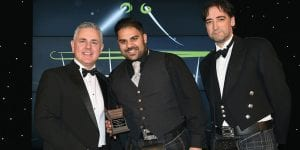 Gavin Anderson, general sales manager (UK & Ireland) of Republic Technologies UK Ltd, left, and awards event host Alistair McGowan, right, present the Scottish Grocer Tobacco Accessories Retailer of the Year Award to Akeil Hussain, Family Shopper, Airbles Street, Motherwell.
