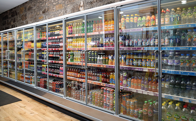 A long bank of glass-fronted chillers runs almost the length of the shop, displaying chilled foods, dairy and soft drinks. At the end of the run are upright freezers containing a range of frozen food.