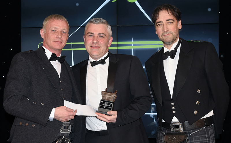 Mike McIver, regional sales manager north, Kerryfresh, left, and awards event host Alistair McGowan, right, present the Scottish Grocer Chilled Retailer of the Year Award to Scott Graham, McLeish, Inverurie, Aberdeenshire.