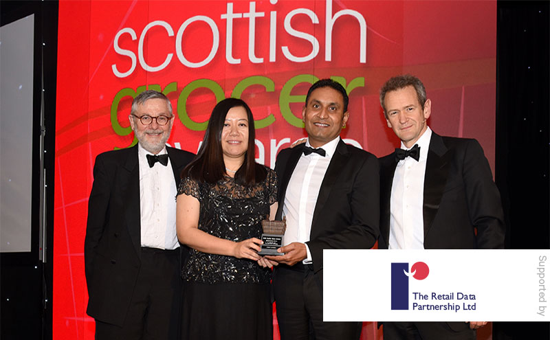 Stephen Burnett, managing director of The Retail Data Partnership and Alexander Armstrong present the Merchandising Award to Mahmood Saleem and Junfang Yun, Ardeer Services.